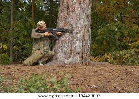 Teenager boy in battle dress and a rifle Air Soft Gun