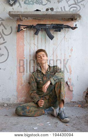 Teenager boy in battle dress of knife and rifle Air Soft Gun