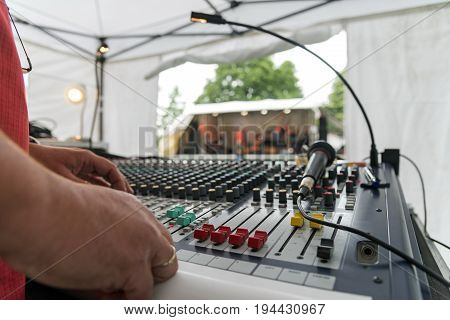Sound mixer at an open air music festival view over the mixing panel with sliders and microphone stage blurred in the background selected focus narrow depth of field