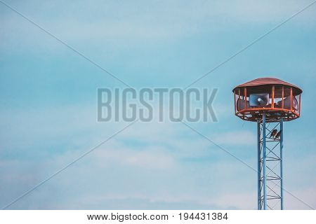 Public speaker tower with two birds perching on against blue sky background and added retro color filter