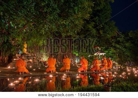 CHIANG MAI THAILAND - JULY 08 2017 :Unidentified monks in ritual around Buddha statue among many candlelight at Phan Tao temple Chiang maiThailand in Asanha Puja Day