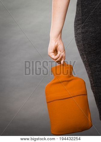 Woman Holds Hot Water Bottle In Red Fleece Cover