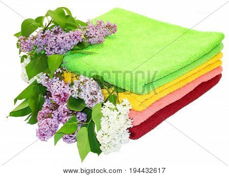 A pile of colorful towels a sprig of white lilac flowers and green leaves on a white background