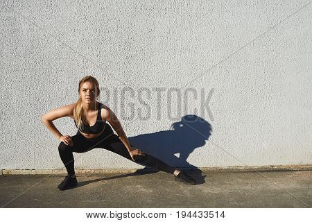 Stylish attractive young female runner in black sportswear doing warm-up routine outdoors before running stretching legs with lunge hamstring stretch exercise. Sports fitness and healthy lifestyle