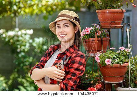 portrait of gardener girl with secateurs in the garden. People, gardening, care of flowers, hobby concept