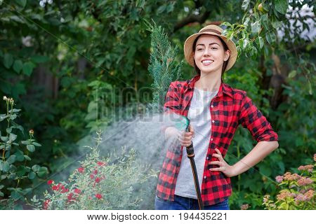 portrait of happy young woman gardener watering garden with hose. People, gardening, care of flowers, hobby concept