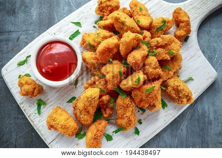Fried crispy chicken nuggets with ketchup on white board.