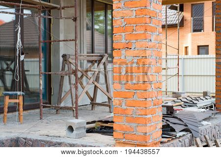 A private house is being constructed. Building a private house with red brick columns