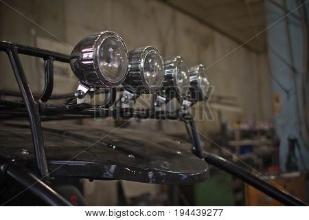 Headlights of black ATV quadbike isolated on city pavement, close up