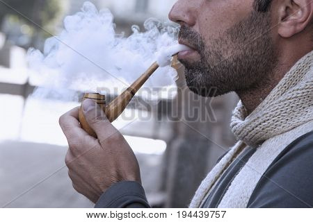 Mature businessman enjoying a moment of contemplation. Mature man smoking a pipe with fragrant tobacco. (Dependence relaxation stress health concept)