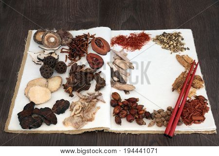 Chinese herb selection used in traditional herbal medicine with chopsticks on a hemp notebook  on oak background.