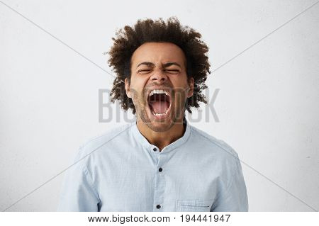 Portrait Of Dark-skinned African Guy With Curly Hair Screaming With Wide Opened Mouth Closing His Ey