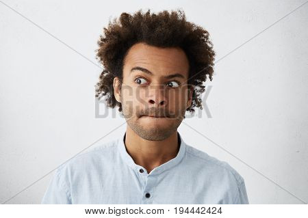 Pleasant-looking Guy With African Hairstyle Having Hesitation Pressing His Lips And Looking Aside Tr