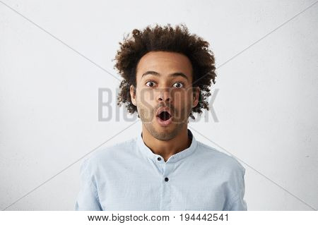 Portrait Of Astonished Male Model With Curly Hair, Dark Eyes And Bristle Opening His Mouth With Surp