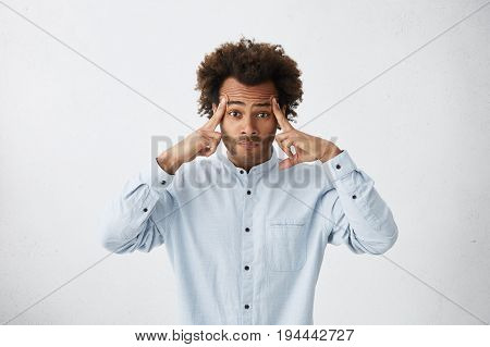 Attractive Male With Bushy Hairstyle Having Thoughtful Look Trying To Concentrate Holding Fingers On