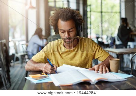 Smart Dark-skinned Student Writing Something Down From Book And Listening To Audio Book In His Headp