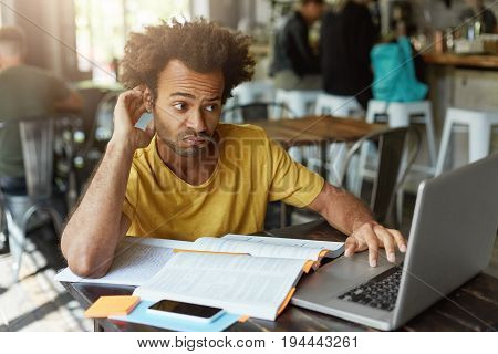 Stylish Student With African Hairstyle Wearing Casual Clothes Having Doubtful Look While Looking At