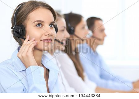 Call center operator in headset while consulting client. Telemarketing or phone sales. Customer service and business concept.