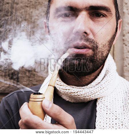 brutal hipster man enjoying pipe smoking (tobacco smoke addiction)