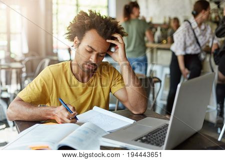 Smart College Student In Casual Clothes Looking Attentively In His Notebook Writing Notes Using Lapt