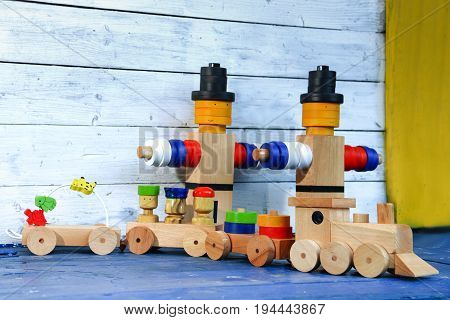 Wooden colorful figures and freight train with loaded wagons