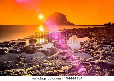 Spectacular colorful sunrise on the beach in front of the Byzantine castle of Monemvasia, Lakonia, Peloponnese, Greece.