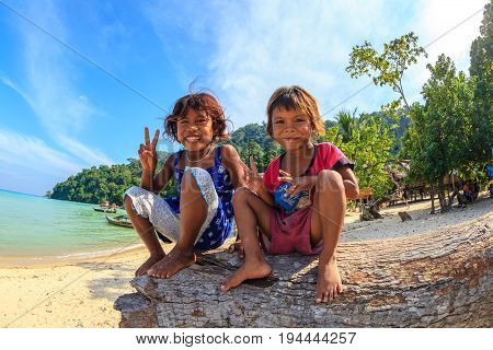 Mu Ko Surin National Park, Thailand - Jannuary 3, 2016: Happy children of Moken ethnic , also called Chao Ley, or Sea Gypsies, sitting on a beach tree in their village.