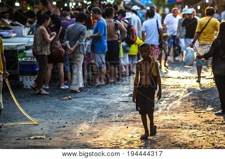 Fish market, Rawai, Phuket, Thailand - January 7, 2016: lonely young boy walking saddly through the Rawai fish market at sunset. Tourists buying fish on background.