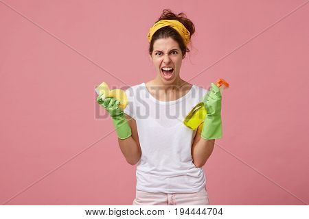 Furious And Annoyed Woman With Yellow Scarf On Head And In Green Gloves Holding Washing Spay And Spo