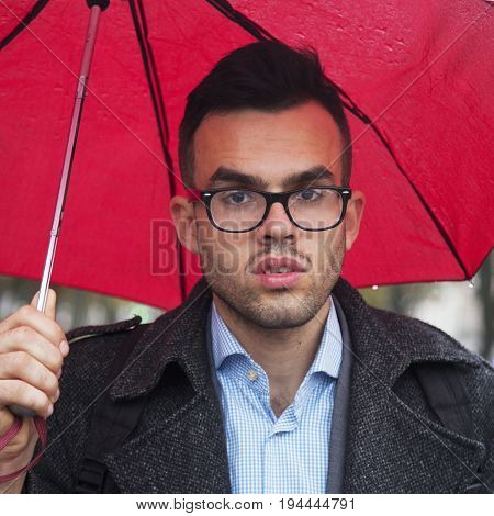 Businessman with red umbrella protecting himself from the rain as symbol of protection from economic crisis (weather business security security concept)