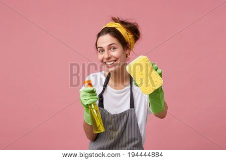 Smiling Housewoman In Apron And Rubber Gloves Showing Tidy Sponge And Detergent Isolated Over Pink B