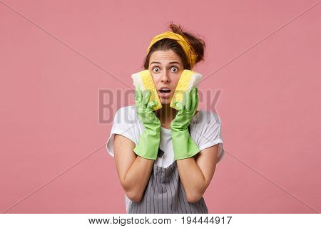 Shocked Female Housekeeper Holding Two Sponges On Cheeks Having Much Work To Do Being In Panic. Cauc
