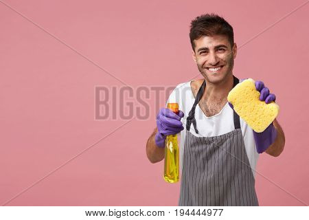 Smiling European Male Dressed In Apron And Rubber Protective Gloves Holding Sponge And Detergent Pos