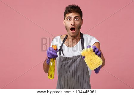 Untidy Janitor Wearing Apron And Rubber Gloves Looking With Bugged Eyes And Jaw Dropped While Doing