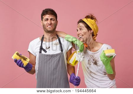 Family Couple Tidying Up Their Apartment: Discontent Male Wearing Apron Holding Dirty Sponge Hating