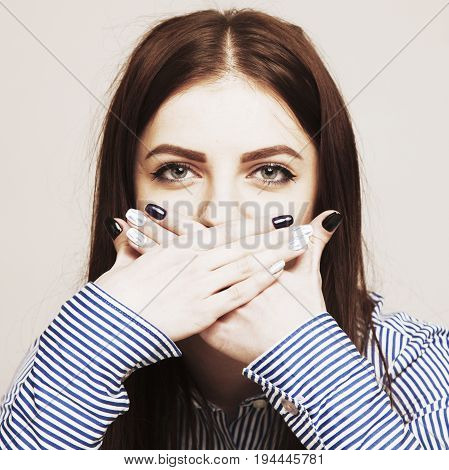 I will not tell you anything. Silence tabu secret mystery communication concept. Woman covering the mouth with her hands. (Gestures psychology body language concept)