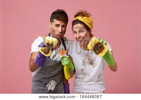 European Couple Wiping Out All Dust With Sponges And Detergent While Standing Against Pink Backgroun