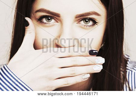 Woman talking and at the same time covering the mouth with her hand as a symbol of deceit and lies (Gestures psychology body language concept)