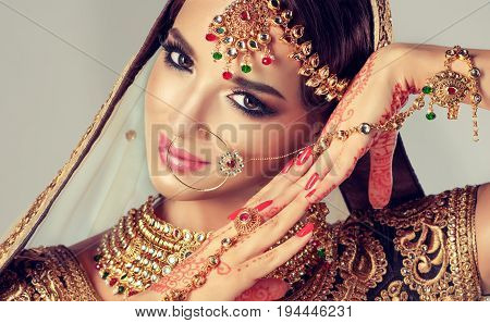 Portrait  smiling of beautiful indian girl. Young indian woman model with golden kundan jewelry set . Traditional Indian costume lehenga choli .