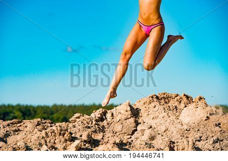 Photo of beautiful model legs jumping in the air on pile of sand and blue sky background