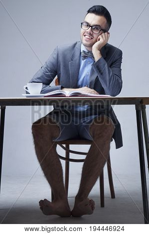 Young businessman with bare feet works in office. (Boss business rules officialdom concept)
