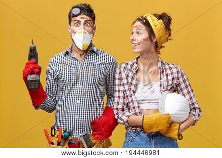 Bug-eyed Male Wearing Protective Mask And Gloves Having Tool Belt On Waist Holding Drill Being Scare