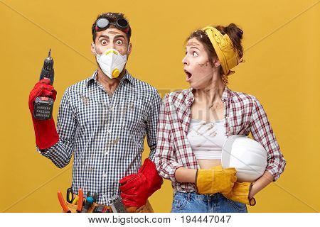 Shocked Woman In Checkered Shirt Holding Helmet Looking At His Husband With Wide Opened Mouth Who Do