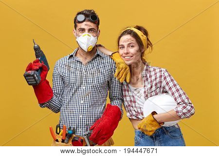 Glad Couple With Dirty Faces Wearing Casual Clothes Holding Drill And Hardhat Doing Repearing In The