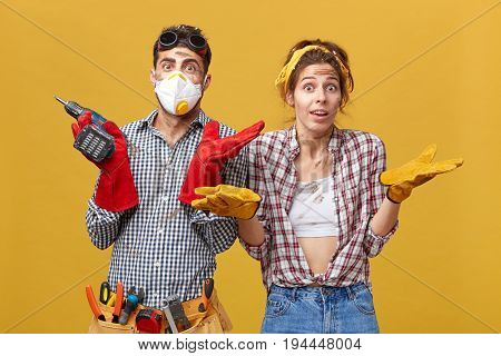 Male And Female Manual Workers Shrugging Their Shoulders With Dubious Expressions Not Knowing What T