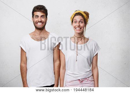 Stylish Bearded Male In T-shirt And Cute Female With Yellow Headband Smiling Unnaturally Showing Thi