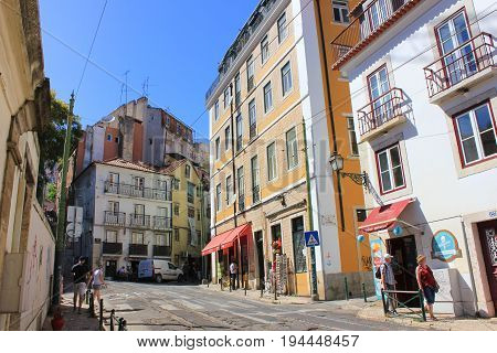 LISBON, PORTUGAL - JUNE 7, 2017: People exploring cosy narrow streets of Alfama. Famous city center tourist travel area, colorful summer bright scene