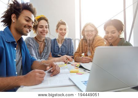 Group Of Five Mixed Race Students Sitting Together Surrounded With Books Looking Happily At Laptop M