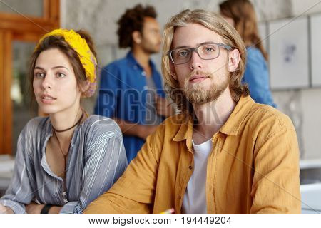 Young Hipster Male Freelancer With Beard Wearing Shirt And Eyewear Having Clever Look Sitting Near H
