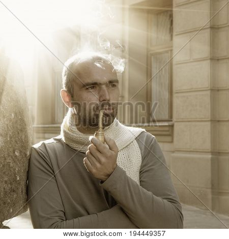 Mature businessman enjoying a moment of contemplation. Mature man smoking a pipe with fragrant tobacco. Retro styled.